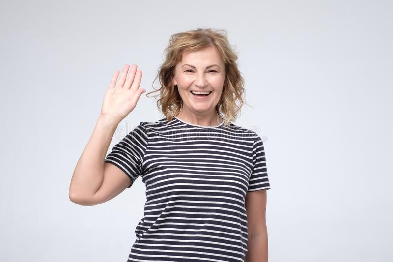 Positive reife kaukasische l?chelnde Frau freundliche und wellenartig bewegende Hand an der Kamera lizenzfreie stockbilder
