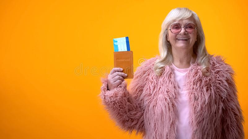 Positive retiree lady showing passport and tickets, visa service, travel agency stock images