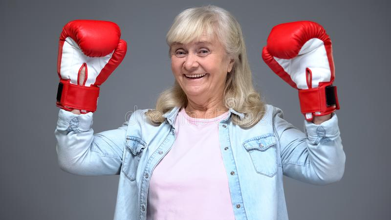 Positive retiree woman in boxing gloves rising hands up, success concept, belief royalty free stock images
