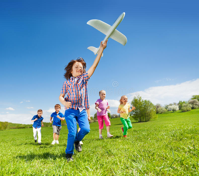 Positive running kids and boy holding airplane toy. Positive running kids with boy holding big white airplane toy in the field during summer sunny day royalty free stock photography