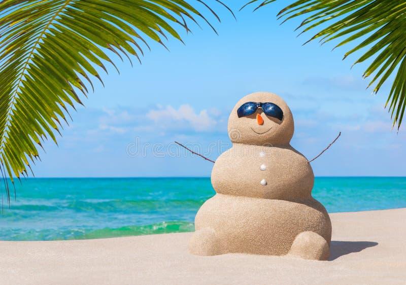 Positive sandy snowman in sunglasses at palm ocean sandy beach stock photo