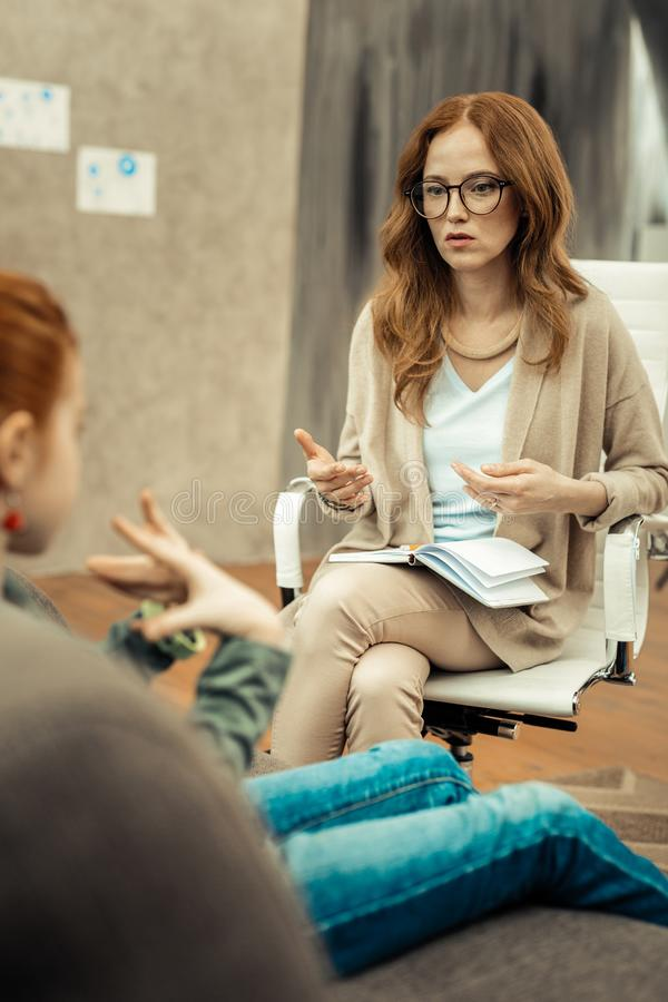 Positive schöne Frau, die mit ihrem Patienten sitzt lizenzfreie stockbilder