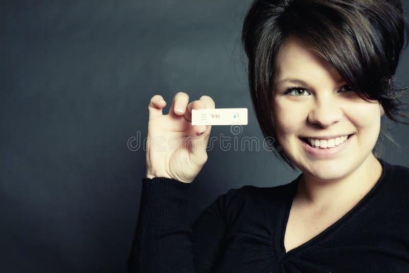 Positive Schwangerschaft-Prüfung und glückliche lächelnde Frau stockbild