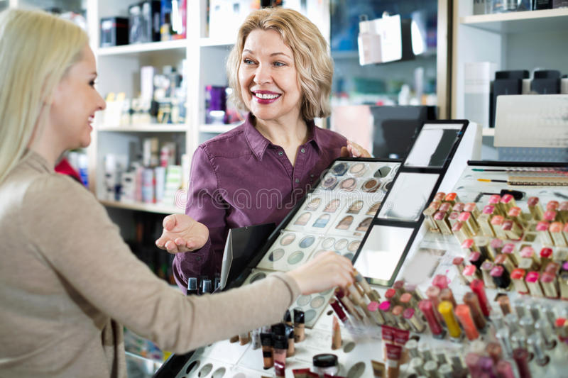 Positive seller helps customers choose cosmetics in store stock photography
