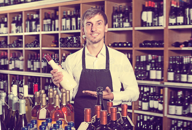 Positive seller man promoting bottle of wine royalty free stock images