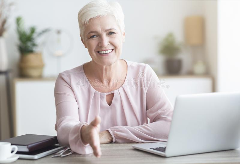 Positive senior business lady giving hand for shaking. Deal is complete, home interior, free space stock photo
