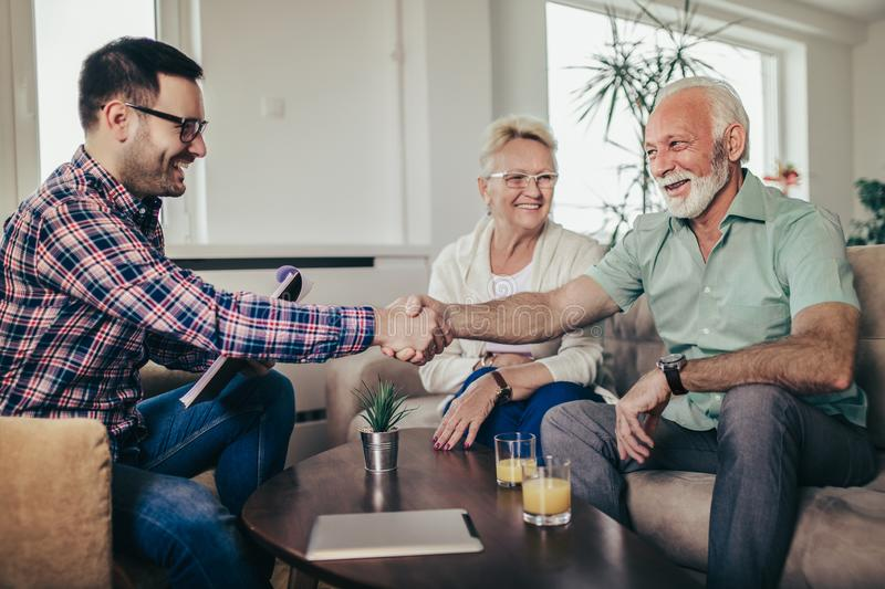 Positive senior couple consulting with insurance agent royalty free stock photography