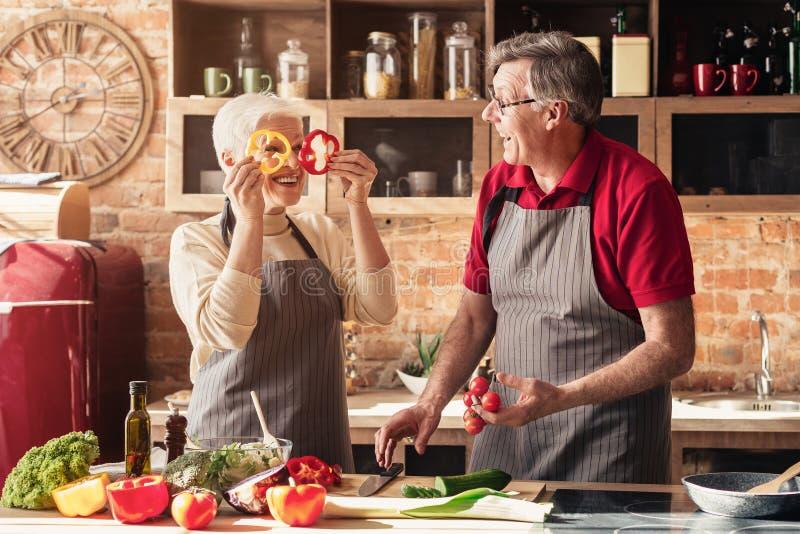 Positive senior couple having fun on kitchen royalty free stock photos