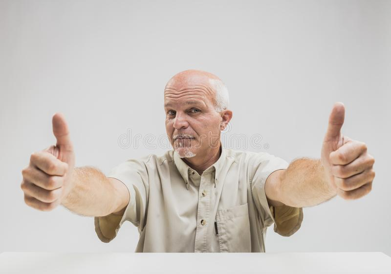 Positive senior man giving a double thumbs up royalty free stock photo