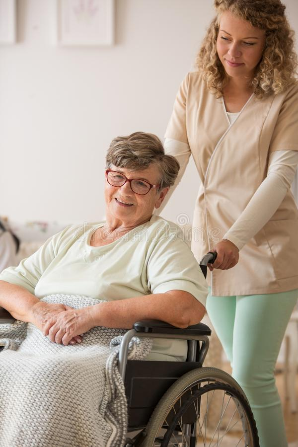 Positive senior patient on wheelchair with supportive nurse stock image