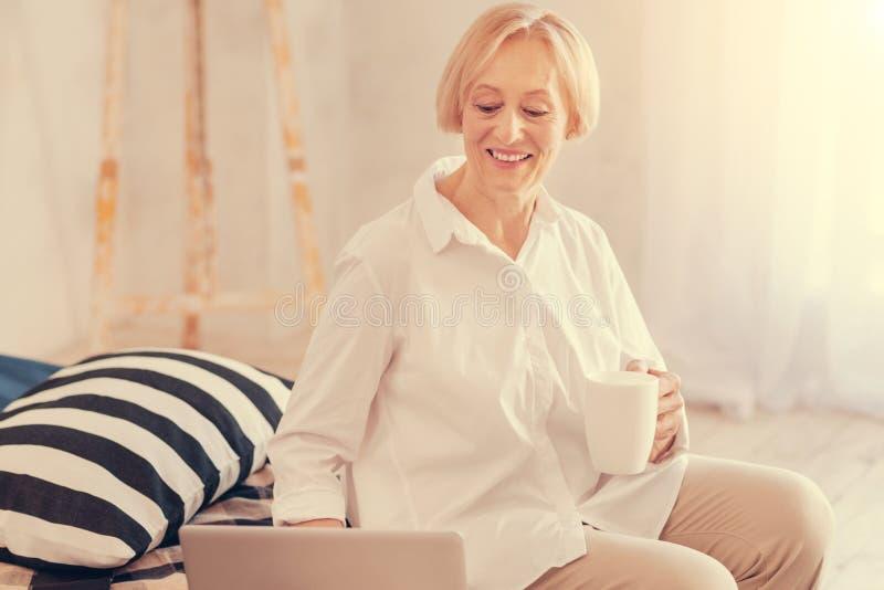 Positive senior woman resting in her bedroom stock photo