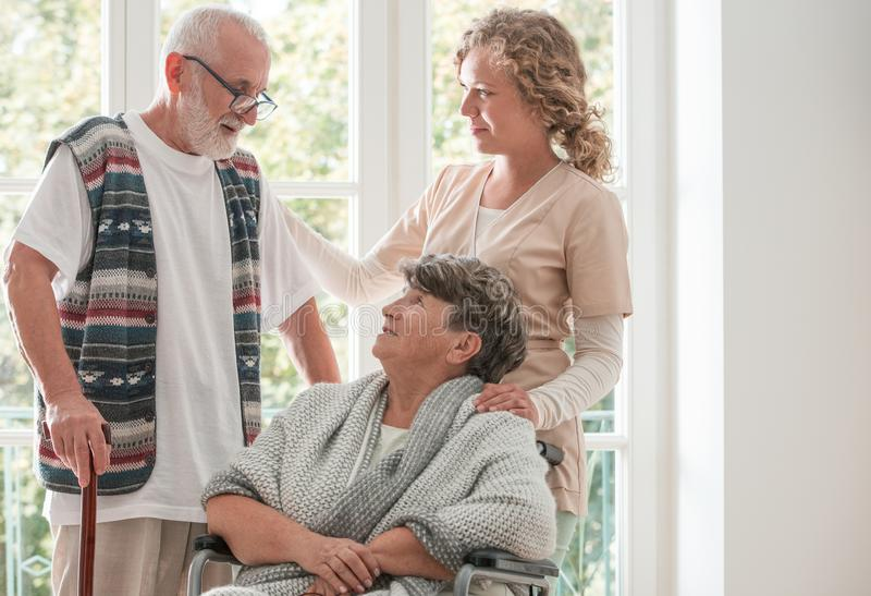 Positive senior woman on wheelchair with caring nurse and elderly friend with walking stick. Positive senior women on wheelchair with caring nurse and elderly stock images