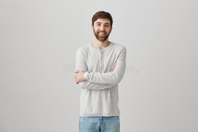 Positive shy good-looking guy with beard standing with crossed hands in pullover over gray background, smiling and royalty free stock photos