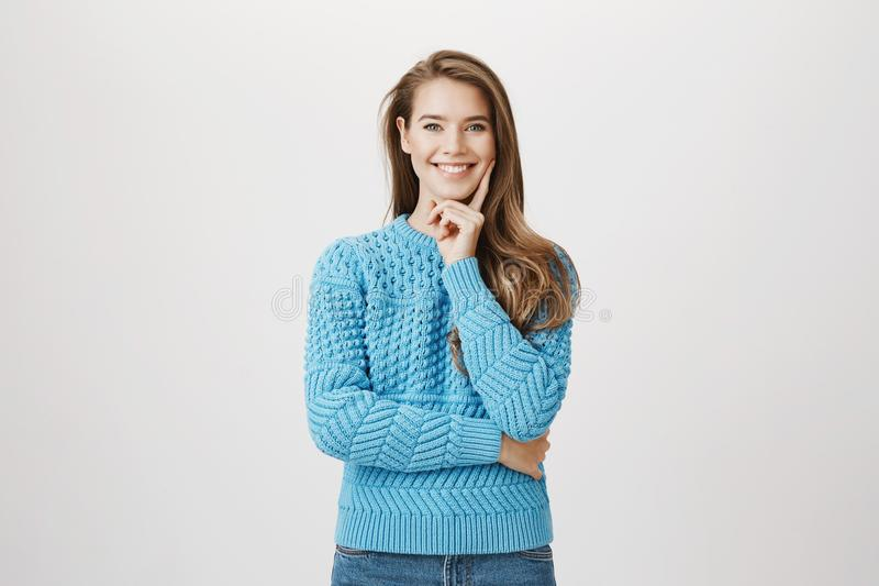 Positive smart caucasian woman, smiling broadly while holding hand on cheek, having great idea or conception in mind royalty free stock photos