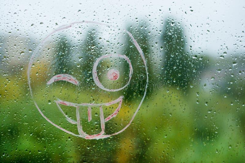 Positive smiley on a rainy autumn window royalty free stock photo