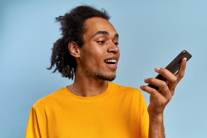 Positive smiling african american young guy talking on smartphone royalty free stock photos