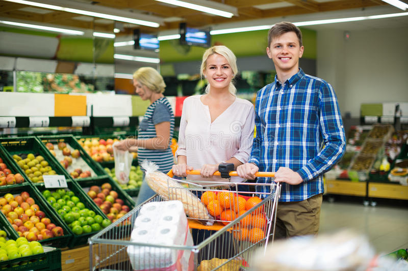 Positive smiling customers choosing fresh frusits stock photos