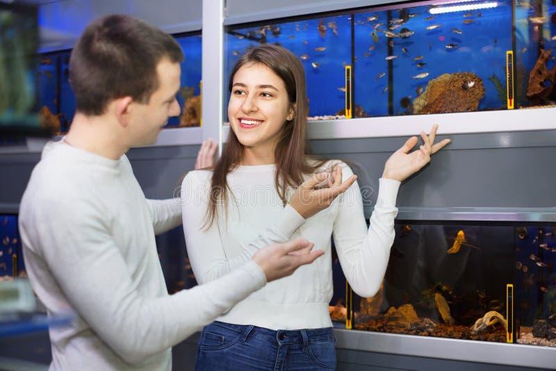 Positive smiling customers selecting tropical fish stock photos