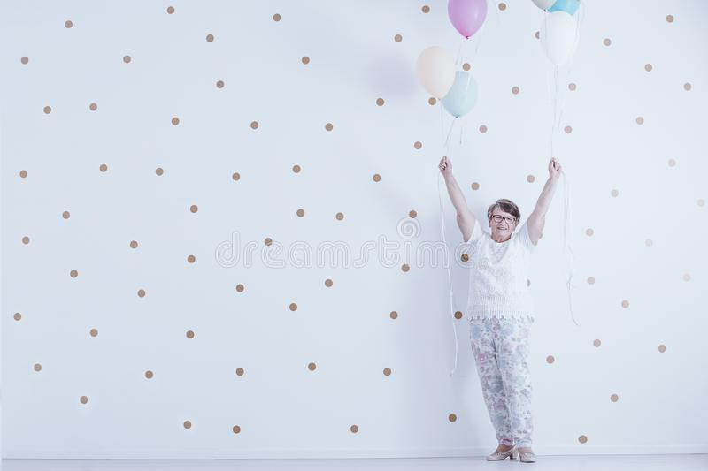 Positive smiling elderly woman with colorful balloons against white wall with gold dots stock images