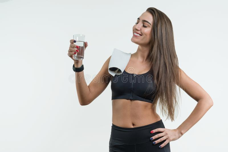 Positive smiling fitness woman drinking water against a white background. royalty free stock images