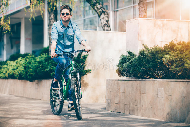 Positive smiling guy riding a bike stock photography