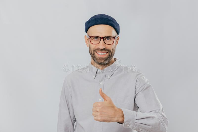 Positive smiling man with stubble, raises thumb up, demonstrates his like and approvement, wears headgear and formal shirt, stock photo