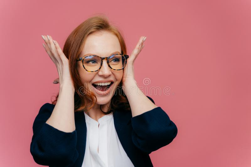 Positive smiling redhead woman covers ears, happy to hear something noisy and funny, wears transparent glasses, black and white royalty free stock images