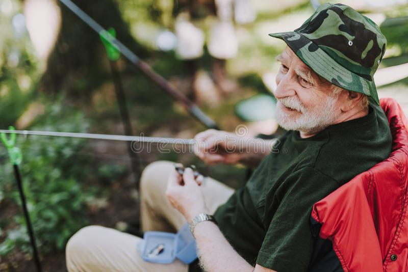 Cheerful elderly man enjoying fishing on the weekend stock photo