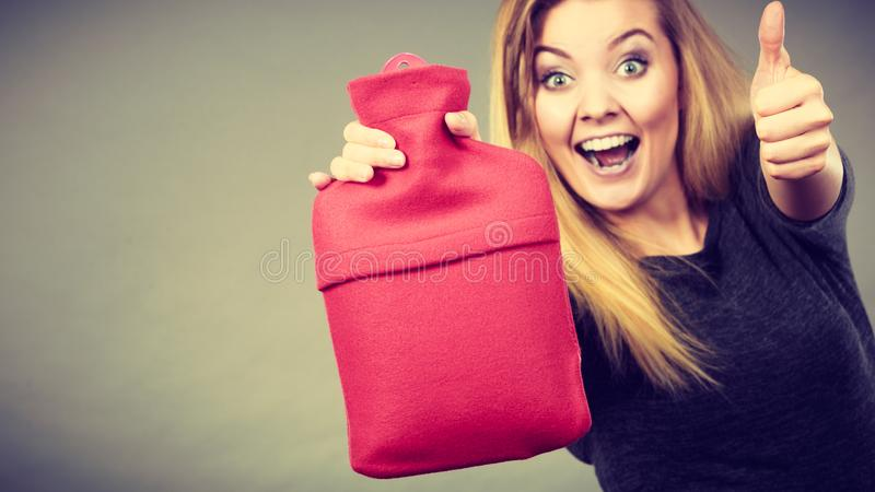 Happy woman holds hot water bottle royalty free stock photography