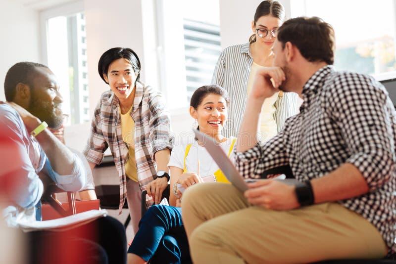 Positive Studenten, die gut an ihrem Geistesblitz lachen und sich fühlen stockfotos