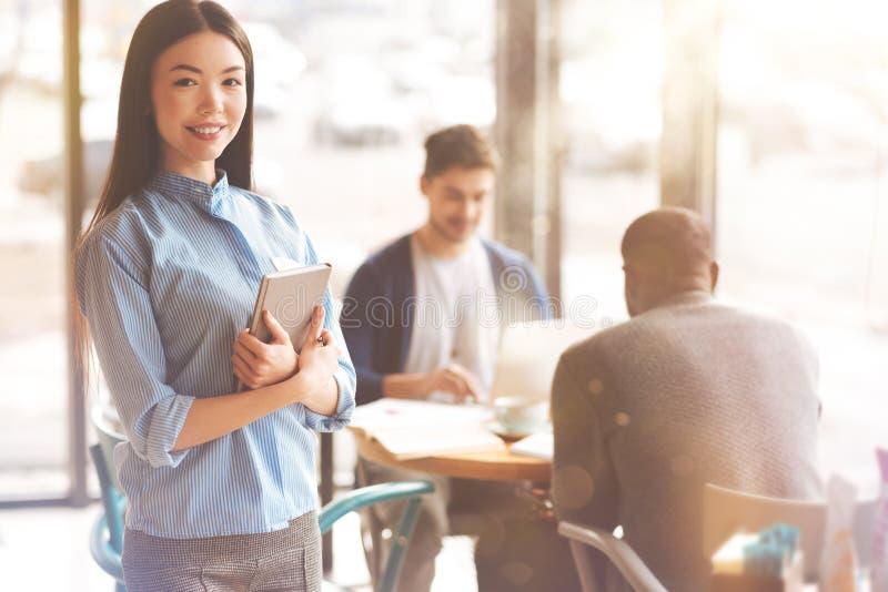 Positive Studentin, die ein Buch hält lizenzfreie stockbilder