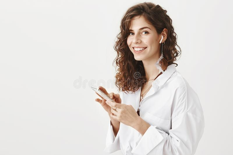 Positive successful caucsian woman talking on smartphone via wireless earbuds, holding device in hand while smiling at royalty free stock photography