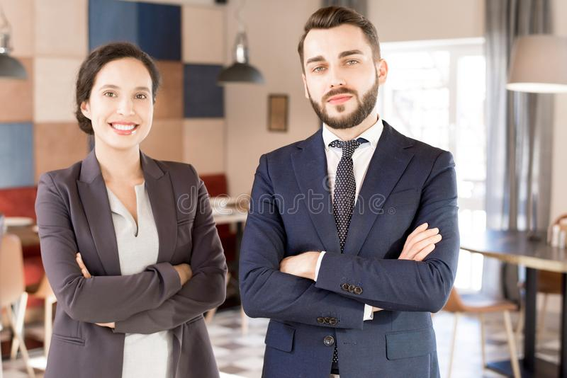 Positive successful multiethnic business partners. Positive successful young multiethic business partners smiling at camera and crossing arms on chest, business royalty free stock image