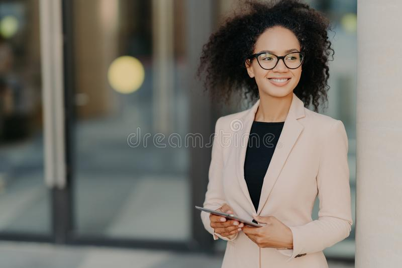 Positive successful woman entrepreneur with Afro hair holds digital tablet, stands outdoor near office building, wears formal stock photography