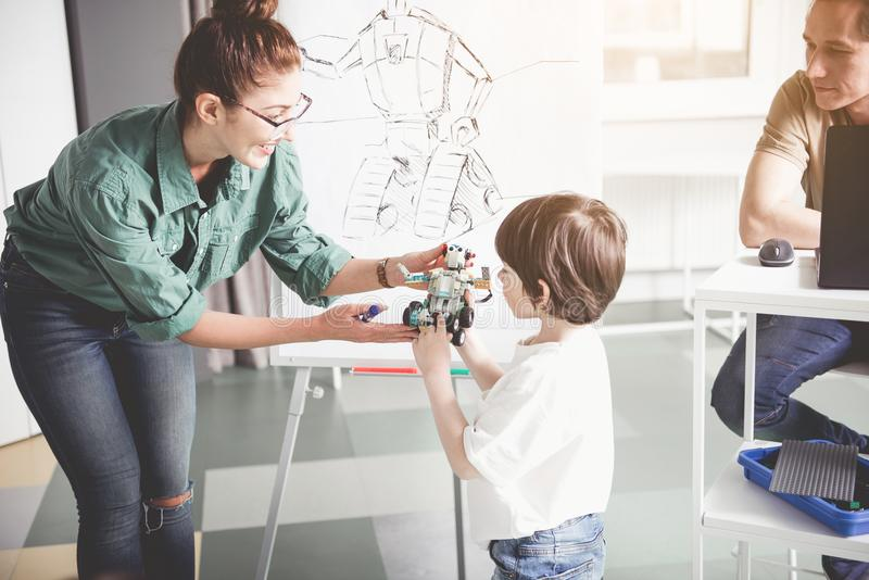Glad woman and child holding toy. Positive teacher giving modern robot happy kid. He telling information about it. Contemporary technology concept stock images