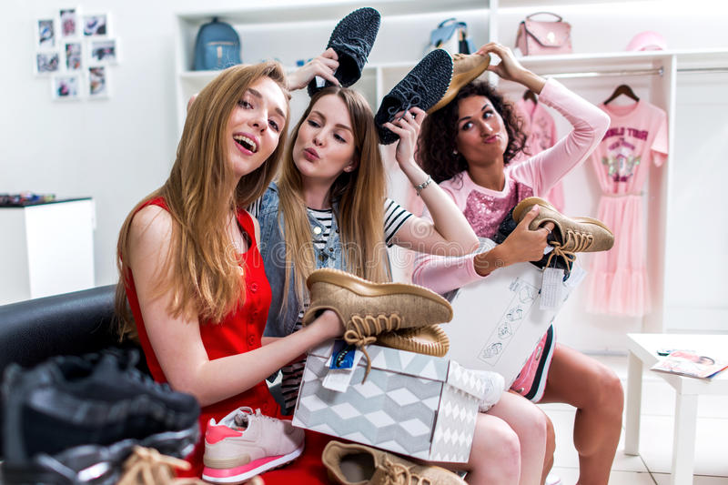 Positive teen girlfriends having fun time together while doing shopping sitting choosing new shoes fooling around and royalty free stock images
