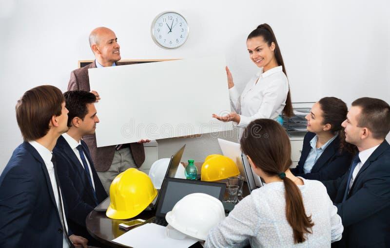 Positive temperamentvolle Kollegen, die Neuentwicklungsplan besprechen stockbild