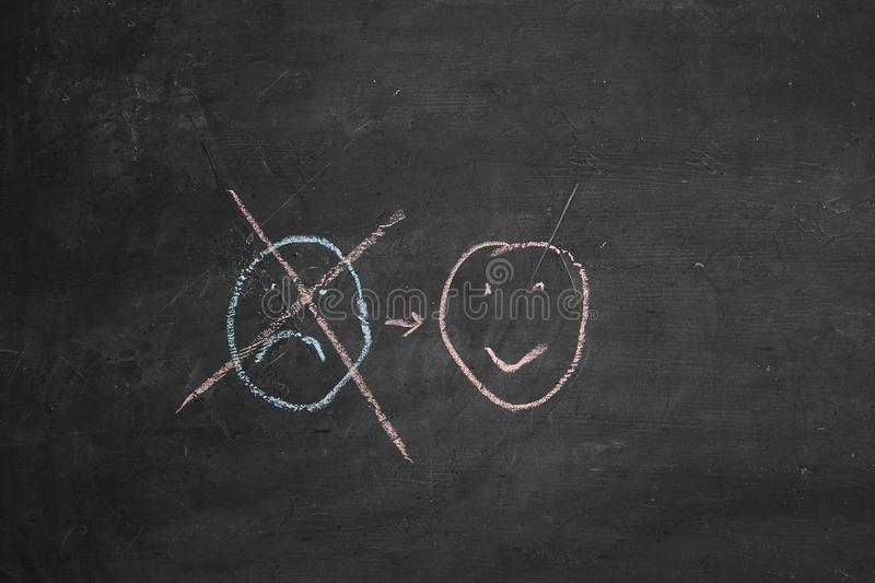 Positive thinking or Attitude and Happy Concept. Hand Drawn A Smiley Face And Sad Emotion on blackboard stock images