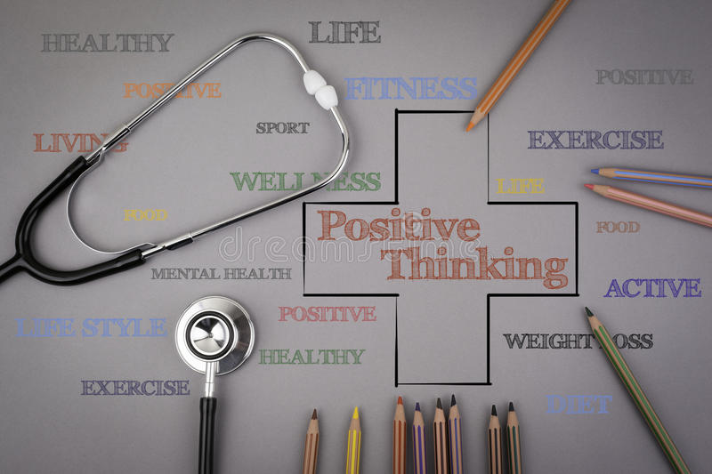 Positive thinking word cloud, health cross concept. Colored pencils and a stetoscope on the table stock photo