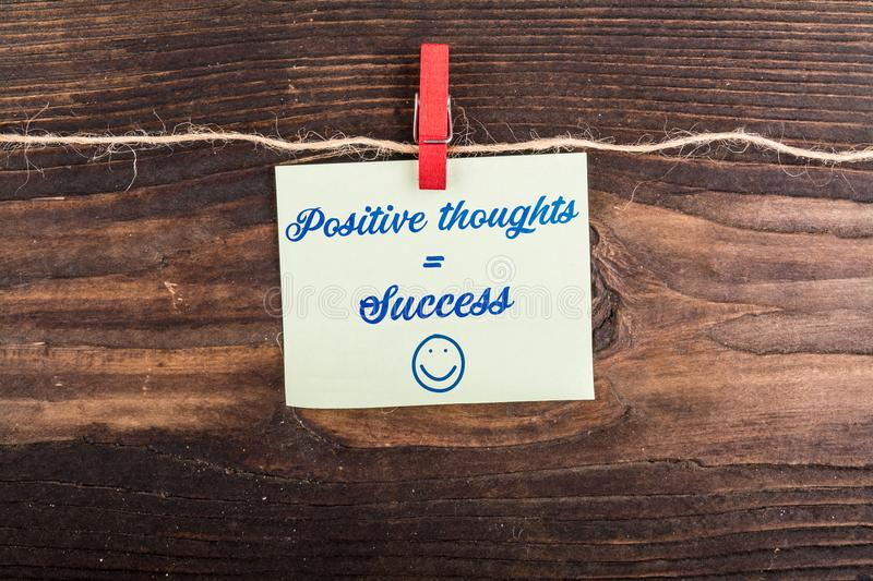 Positive thoughts Equal success. Write in sticky note with clothes pin and rope on wood royalty free stock images