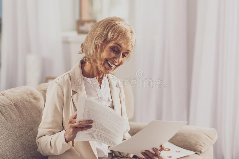 Happy mature woman checking documents royalty free stock photography