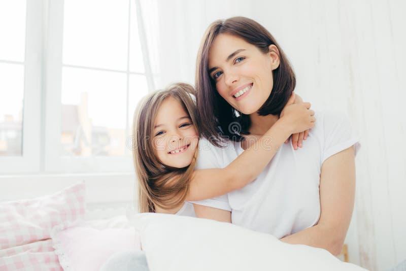 Positive Tochter und Mama umfassen sich und sind in der Heiterkeit nach gutem Schlaf, aufwerfen im Schlafzimmer, Lächeln leicht a stockfoto