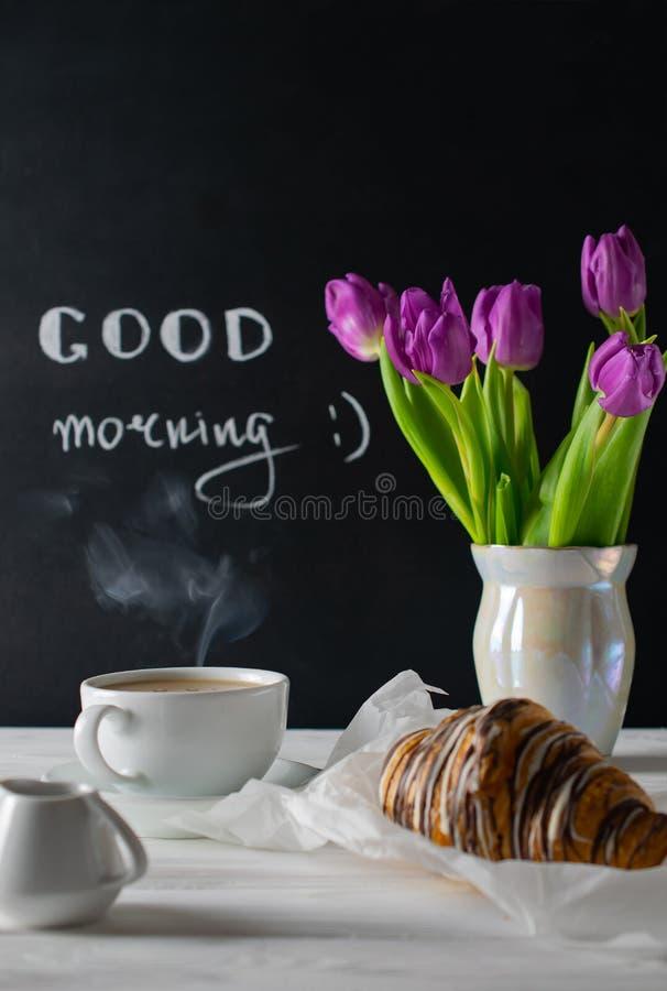 Positive und glückliche Frühstückseinstellung mit den Tulpen bouquest, Kaffee und Hörnchen Guten Morgen stockbild