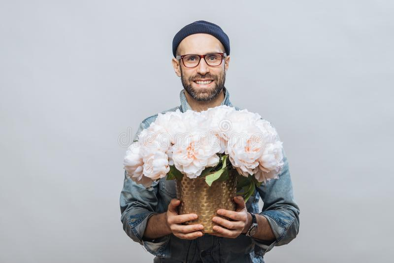 Positive unshaven male wears spectacles, holds beautiful bouquet of flowers, going to present them to his wife and congratulate wi royalty free stock image