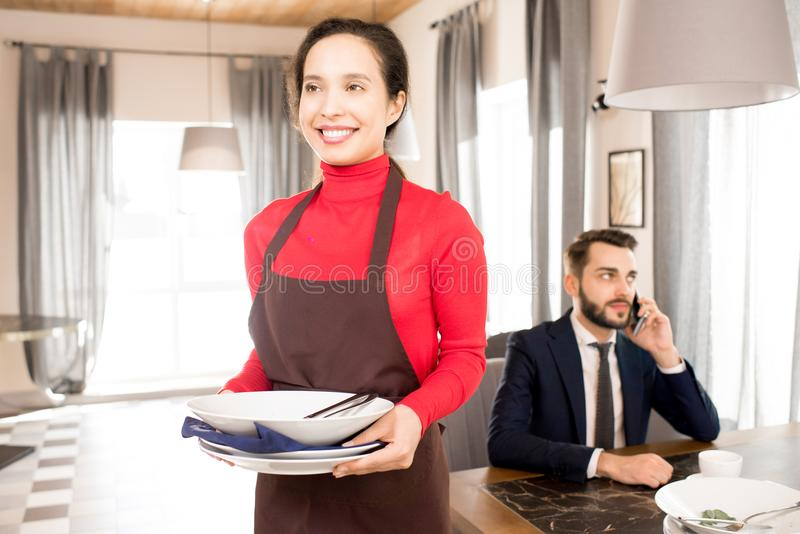 Positive waitress carrying dirty dishes away. Cheerful positive young mixed race waitress in apron carrying dirty dishes from businessmens table after lunch royalty free stock images