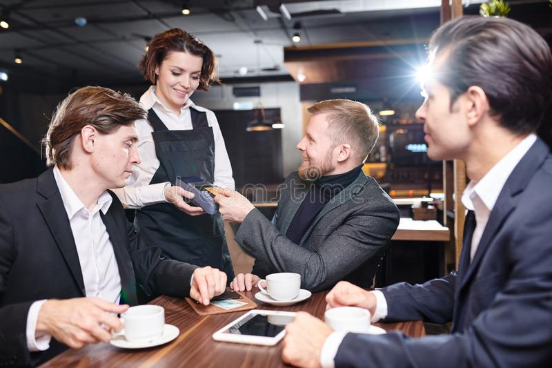 Positive waitress giving payment terminal to business guests in stock images