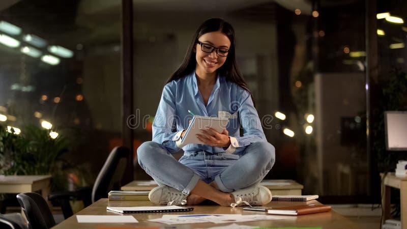Positive weibliche sitzende Lotoshaltung, die in Notizbuch, modernes Arbeitsumfeld schreibt lizenzfreie stockbilder
