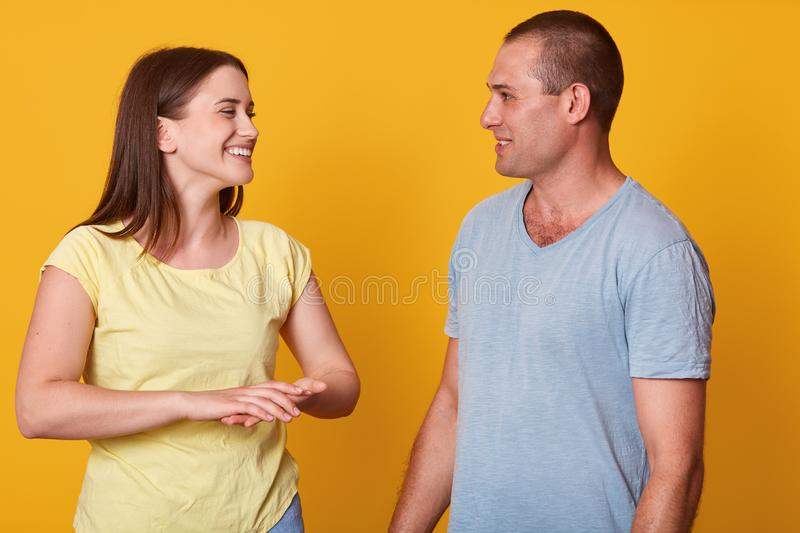 Positive well kept young woman laughing sincerely, listening to her boyfriend attentively, looking at him with interest, keeping royalty free stock image