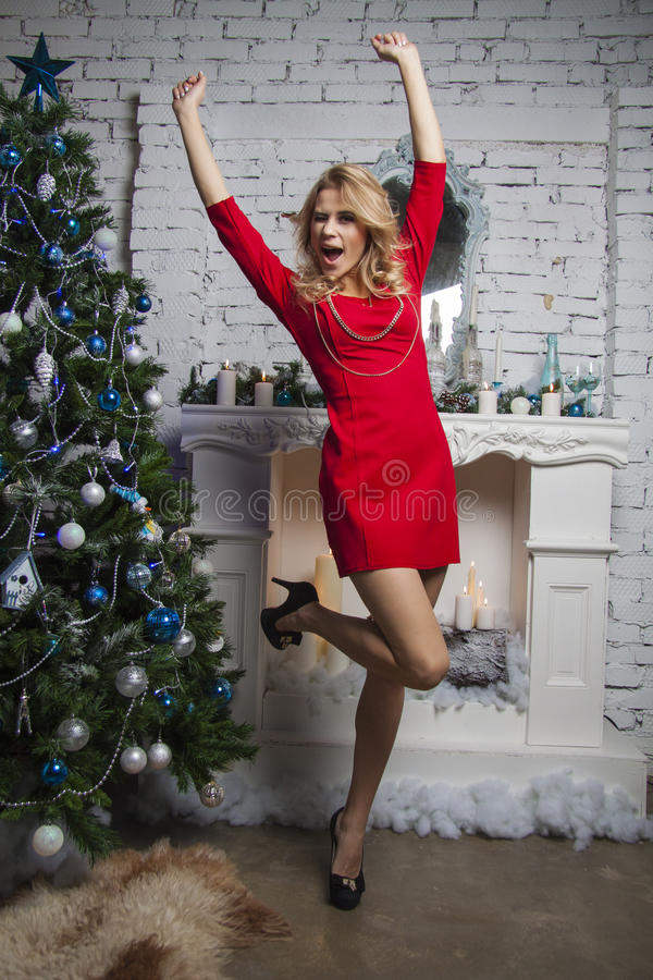 Positive winner Girl in red party dress near new year tree. Girl in red party dress standing straight and posing in studio stock image