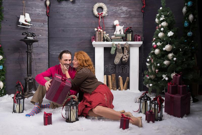 Positive woman being grateful to her husband for pleasant Christmas gift. Moments of happiness. Full length of charming middle aged women kissing her positive stock photos